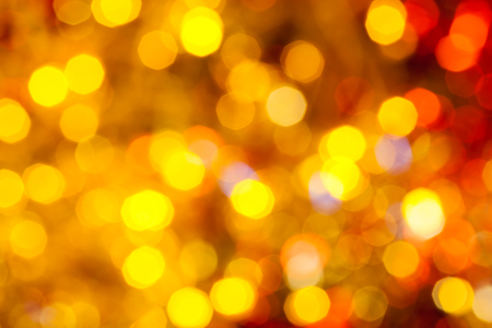 scintillating: abstract blurred background - brown, yellow and red Christmas lights bokeh of electric garlands on Xmas tree