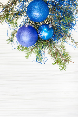 christmas tree decoration: Christmas greeting card - border from three blue and violet Xmas baubles and tree branch on blank paper background
