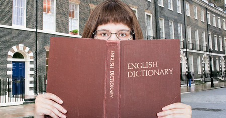 English dictionary: girl with spectacles looks over English Dictionary book and london street on background