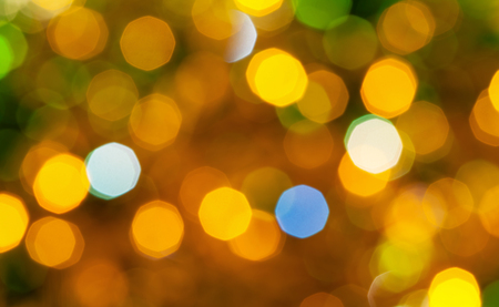 agleam: abstract blurred background - brown and green shimmering Christmas lights bokeh of electric garlands on Xmas tree