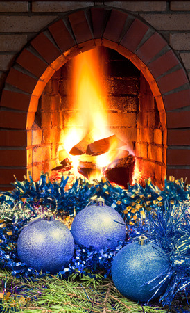 hotbed: blue Christmas balls on green spruce tree with open fire in home fireplace