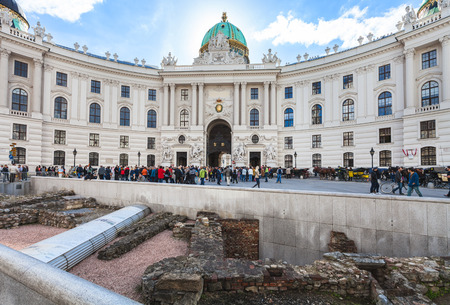outpost: VIENNA, AUSTRIA - SEPTEMBER 27, 2015: ruin of ancient Roman military camp in Vindobona celtic settlement on Michaelerplatz square and tourists near St. Michael wing of Hofburg Palace in Vienna Austria