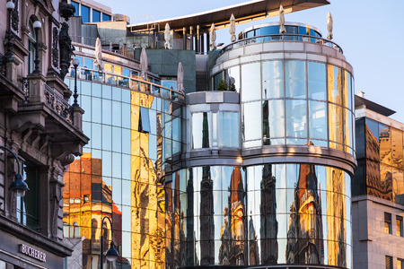 window reflection: VIENNA, AUSTRIA - SEPTEMBER 28, 2015: reflection of St Stephen Cathedral in wall of Haas House on Stephansplatz in Vienna. Haas-haus was designed by architect Hans Hollein and was completed in 1990