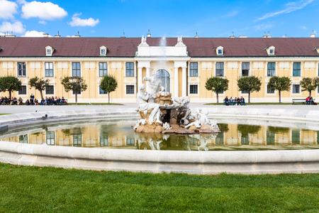 schloss schonbrunn: VIENNA, AUSTRIA - SEPTEMBER 29, 2015: tourists on benches near fountain in Schloss Schonbrunn palace garden. Schonbrunn Palace is former imperial summer residence located Vienna city.