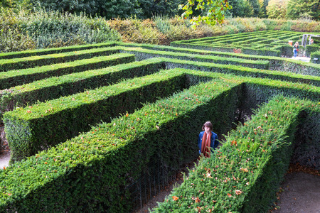 VIENNA, AUSTRIA - SEPTEMBER 29, 2015: tourists in green maze of Schloss Schonbrunn palace garden. The Maze at Schonbrunn was laid out between 1698 and 1740 and consisted of four different parts