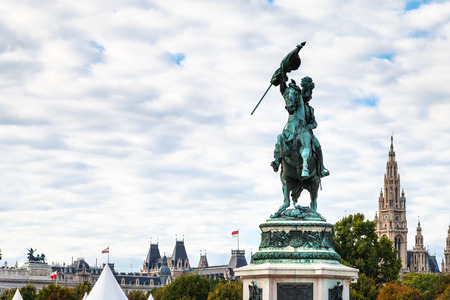 archduke: travel to Vienna city - statue of Archduke Charles on Heldenplatz square and view of Rathaus in Vienna, Austria