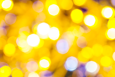 agleam: abstract blurred background - light yellow and violet flickering Christmas lights bokeh of electric garlands on Xmas tree Stock Photo