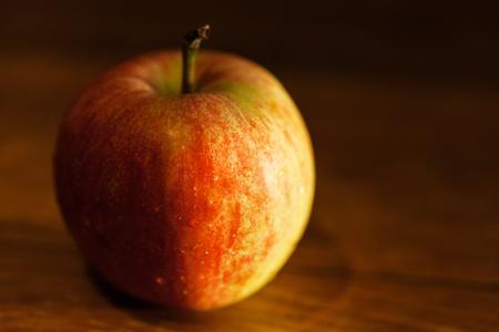 dark red: ripe apple on wooden table illuminated by evening sun