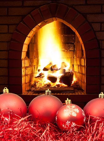 hotbed: red Christmas balls and tinsel with open fire in home fireplace