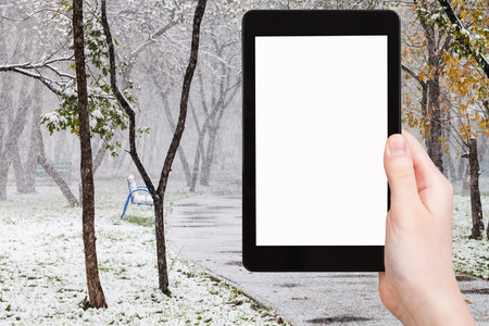 blank tablet: season concept - hand holds tablet pc with cut out screen and first snowfall in public garden on background Stock Photo