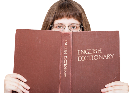 english dictionary: girl with glasses looks over English Dictionary book isolated on white background