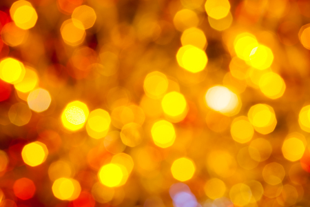 agleam: abstract blurred background - brown, yellow and red flickering Christmas lights bokeh of electric garlands on Xmas tree Stock Photo