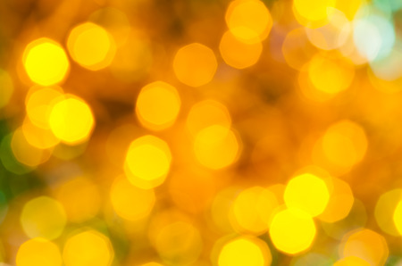 agleam: abstract blurred background - yellow and green dark flickering Christmas lights bokeh of electric garlands on Xmas tree