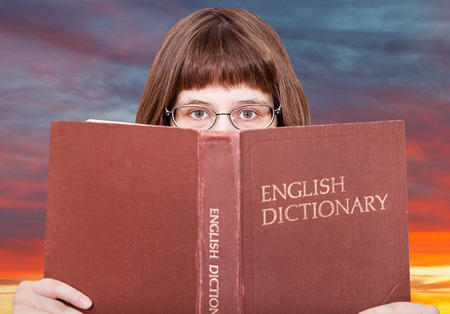 english dictionary: girl with spectacles looks over English Dictionary book and red yellow sunset sky on background