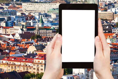 advertising: travel concept - tourist photographs Bratislava city skyline on tablet pc with cut out screen with blank place for advertising logo