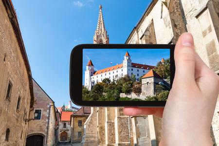 snapshot: travel concept - tourist snapshot of Bratislava Hrad castle from Farska street in old town on smartphone