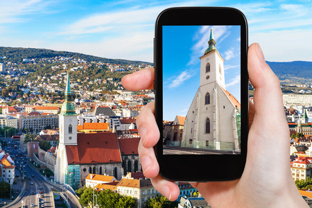 hand hold: travel concept - tourist snapshot of facade of St. Martin Cathedral in Bratislava town on smartphone