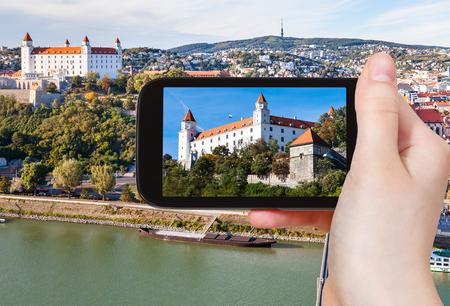 snapshot: travel concept - tourist snapshot of Bratislava Hrad Castle over Danube River waterfront on smartphone Editorial