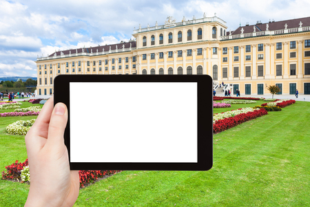 schloss schonbrunn: travel concept - tourist photographs of lawn in Schloss Schonbrunn palace in Vienna on tablet pc with cut out screen with blank place for advertising