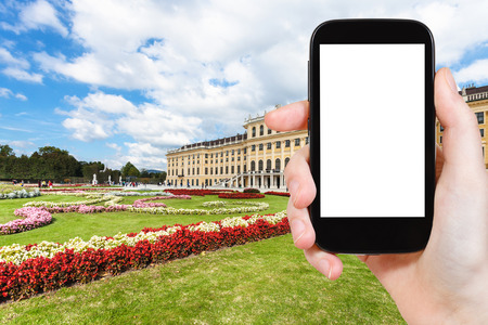 schloss schonbrunn: travel concept - tourist photographs of garden in Schloss Schonbrunn palace in Vienna on smatphone with cut out screen with blank place for advertising Editorial