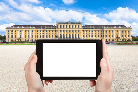 schloss schonbrunn: travel concept - tourist photographs of Schloss Schonbrunn palace in Vienna on tablet pc with cut out screen with blank place for advertising