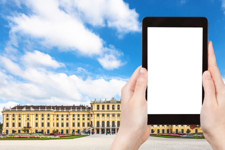 schloss schonbrunn: travel concept - tourist take photo of Schloss Schonbrunn palace in Vienna on tablet pc with cut out screen with blank place for advertising Editorial