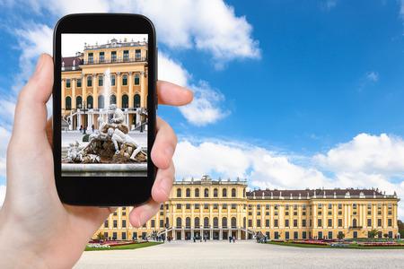 schloss schonbrunn: travel concept - tourist snapshot of fountain near Schloss Schonbrunn palace in Vienna on smartphone