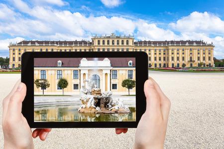 schloss schonbrunn: travel concept - tourist take picture of fountain near Schloss Schonbrunn palace in Vienna on tablet pv