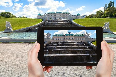 snapping fingers: travel concept - tourist snapshot of upper fountain cascade in Belvedere palace garden in Vienna on tablet pc Editorial