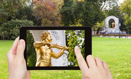 snapshot: travel concept - tourist snapshot of monument of Johann Strauss son in Stadtpark (City Park) in Vienna on tablet pc