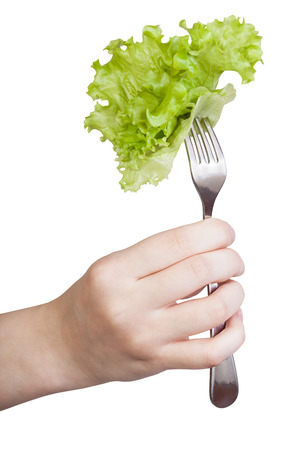 fresh leaf: female hand holds fork with impaled fresh leaf lettuce isolated on white background