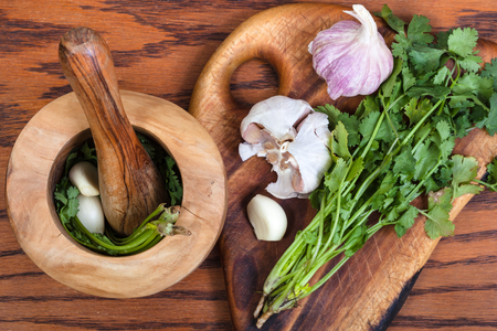 seasonings: cooking seasonings - above view of wooden mortar with cilantro herb and garlic on table Stock Photo