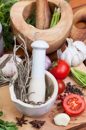 seasonings: cooking seasonings - top view of pestle herbs in ceramic mortar and spices on table Stock Photo