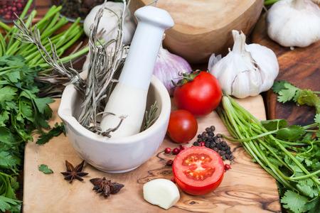 seasonings: cooking seasonings - ceramic mortar with pestle greens on table Stock Photo