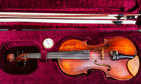 hygrometer: top view of old wooden violin with bow in red velvet case