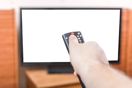 on looker: Hand turns off TV with cut out screen by remote control in living room Stock Photo