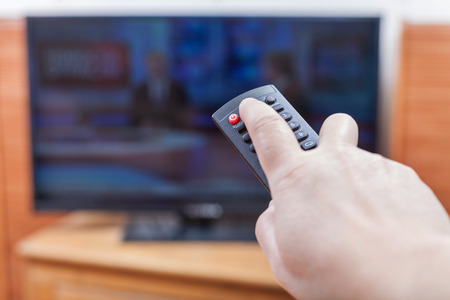 on looker: Hand turns on News on TV by remote control in living room Stock Photo