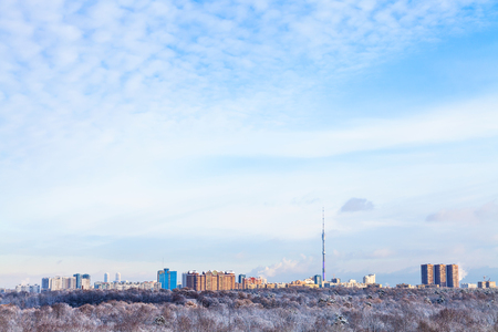 the sky with clouds: blue sky with white clouds over urban houses and TV tower illuminated by evening sun in winter season