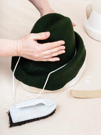 workshop for alpine felt hat making - hatter fixes a felt hood on wooden dummy for shaping