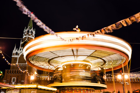 turnabout: MOSCOW, RUSSIA - DECEMBER 6, 2015: Spasskaya tower of Kremlin and Merry-go-round carousel on Red Square on Moscow Christmas Fair in night. Red Square is the central historical square in Moscow.