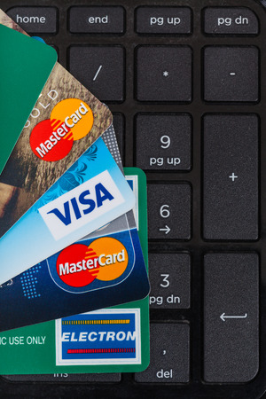 mastercard: MOSCOW, RUSSIA - DECEMBER 8, 2105: top view of plastic VISA and MasterCard, VISA ELECTRON credit and debit cards on black laptop keypad.