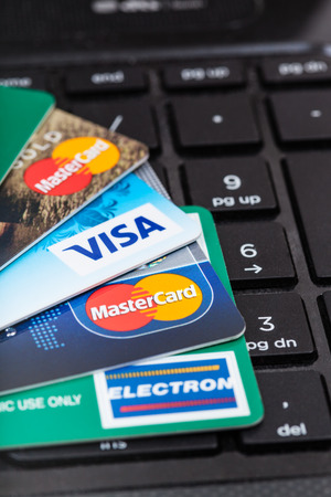 electronic card: MOSCOW, RUSSIA - DECEMBER 8, 2105: plastic VISA and MasterCard, VISA ELECTRON credit and debit cards on black computer keyboard.
