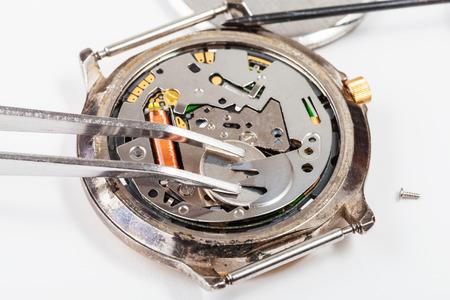 replacing: Repairing of watch - replacing battery in quartz watch by tweezers close up
