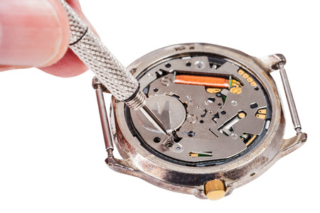 replaces: Repairing of watch - watch repairer replaces battery in quartz wristwatch isolated on white background