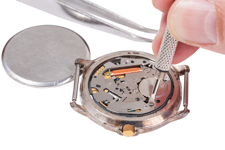 replaces: Repairing of watch - watchmaker replaces battery in quartz wristwatch isolated on white background