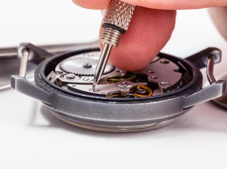 repairer: adjusting old mechanic wristwatch - watch repairer repairs old watch close up