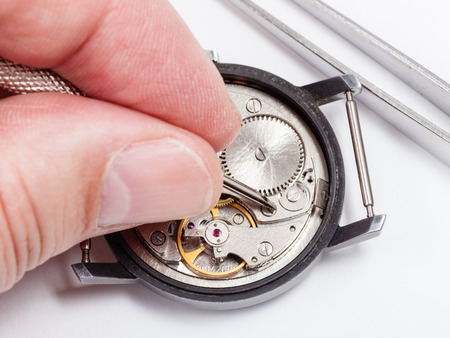 watchmaker: adjusting old mechanic wristwatch - watchmaker repairs old watch close up