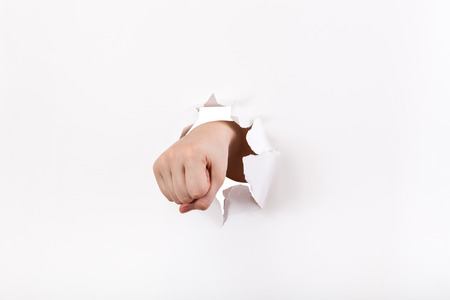 orifice: direct view of the fist breaks a paper wall Stock Photo