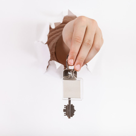 orifice: hand holds the keychain through a hole in a sheet of paper