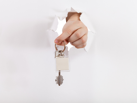 orifice: hand holds the key through a hole in a sheet of paper